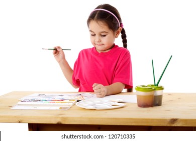 Inspired little girl who draws with watercolors at the table, isolated on white