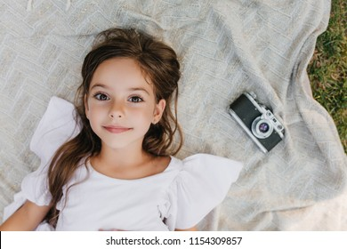 Inspired little lady with big brown eyes lying on blanket in garden and looking up with gently smile. Overhead portrait of dark-haired girl in white dress relaxing on the ground near camera.