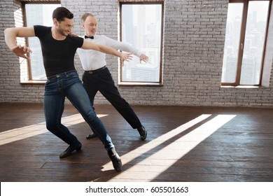 Inspired mature dance instructor teaching aged man at the ballroom
