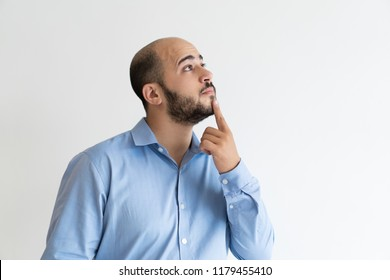 Inspired pensive businessman studying new offer. Bearded man in formal shirt touching chin with finger, thinking and looking at copy space near him. Advertising concept
