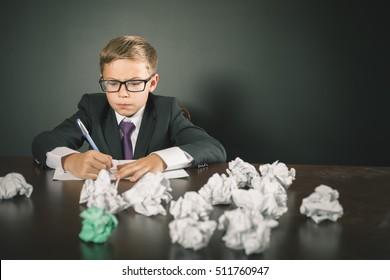 Inspired school boy writing essay or exam