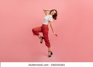 Inspired slim girl dancing on pink background. Studio shot of graceful trendy woman in black shoes.