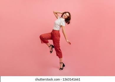 Inspired slim girl dancing on pink background. Studio shot of graceful trendy woman in black shoes.