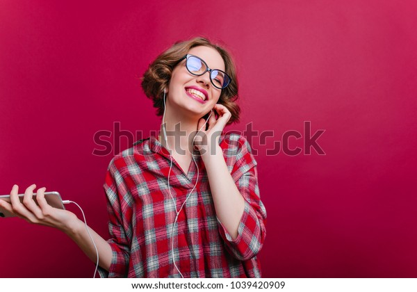 Inspired stylish girl in glasses laughing while listening music on claret background. Place for text. Studio shot of pleased young lady wears casual clothes and enjoying photoshoot.