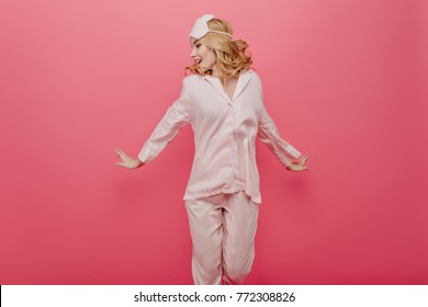 Inspired white woman jumping in morning, enjoying new day. Indoor portrait of positive girl in sleepwear and eyemask having fun.