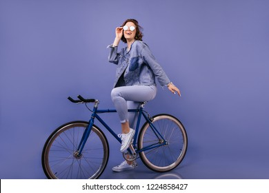 Inspired white woman sitting on bicycle in studio. Indoor portrait of confident lady with wavy hair posing on purple background.