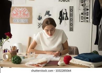 Inspired woman fashion designer drawing sketches with brush at workplace, needlewoman works in studio workshop on new clothes collection ideas, creating ethnic cross-stitch embroidery design pattern