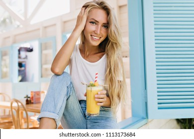 Inspired woman with long hairstyle holding glass of juice and posing with smile. Portrait of tanned blonde model in jeans sitting on sill and drinking cocktail.
