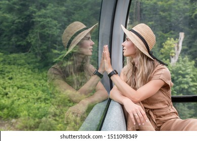 Inspired young beautiful woman admires stunning unique natural views while sitting on a funicular. Admired Caucasian Woman Enjoys Exotic Summer Vacation. Concept of vacation and unity with nature