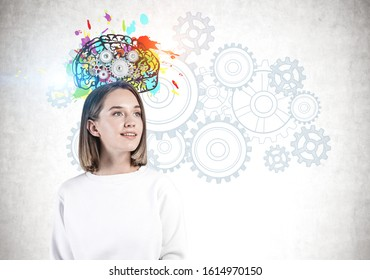 Inspired young girl in casual clothes standing near concrete wall with bright brain sketch with gears drawn on it. Concept of brainstorming