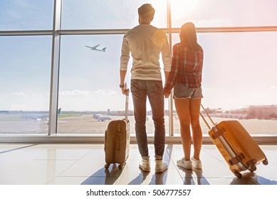 Inspired young loving couple is looking at flying plain in sky. They are standing near window at airport and holding hands