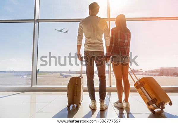空を飛ぶ平原を見つめる若い恋人たち。彼らは空港の窓際に立って手を握っている