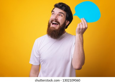 Inspired young man with beard looking away and having an idea bubble over yellow backgorund