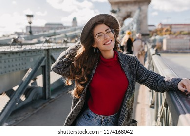 Inspired young woman with dark-brown hair and beautiful eyes looking at river, standing on bridge. Trendy female tourist in hat enjoying warm windy day in Europe.