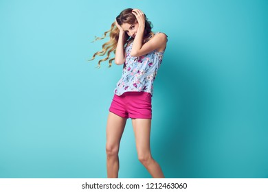 Inspired Young woman laughing dance in Studio. Blonde lovable Girl Having Fun, Trendy Wavy Hairstyle, Stylish fashion pink shorts. Long-haired Model with Happy positive emotion
