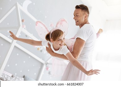 Inspiring active father helping his daughter flying