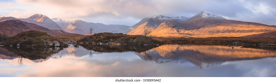 An inspiring wide panorama mountain landscape reflected on a calm peaceful lake at Rannoch Moor near Glencoe in the Scottish Highlands, Scotland.