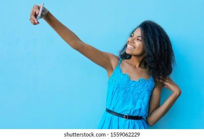 Insta girl. Close up photo of beautiful young African girl, who smiles broadly while looking at the camera of her phone, which she holds in her right stretched arm and takes a selfie.