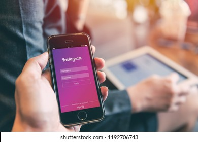 Instagram App on iPhone with people using tablet background closeup male hand hold social network on smart device concept.23 September 2018,Bangkok Thailand.
