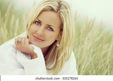 Instagram filter style photograph of a beautiful blond haired blue eyed girl or young woman wearing a white toweling robe sitting in tall grass