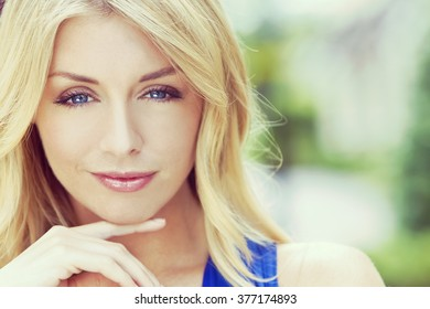 Instagram filter style portrait of naturally beautiful woman in her twenties with blond hair and blue eyes, shot outside in natural sunlight