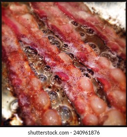 Instagram filtered close up image of frying bacon