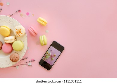 instagram food photography of tasty colorful macarons in plate and phone on trendy pastel pink paper flat lay. space for text. modern photo workshop. holiday catering