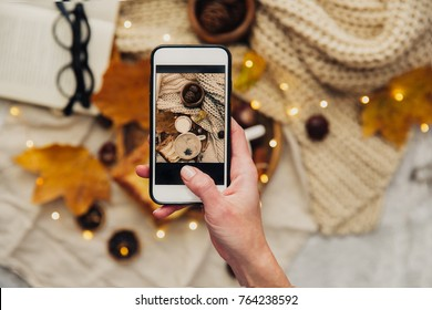 Instagram photography blogging  concept. hand holding phone taking photo of stylish winter flat lay. cozy mood autumn.
