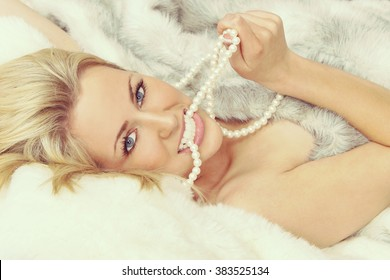 Instagram style beautiful young blond woman in bed wrapped in (fake) fur and biting a pearl necklace