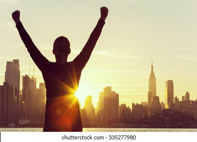 Instagram style filter silhouette of a successful woman or girl arms raised celebrating at sunrise or sunset in front of the New York City Skyline