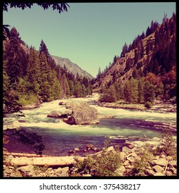 Instagram style image with vintage filter of a river in the mountains of Washington State.