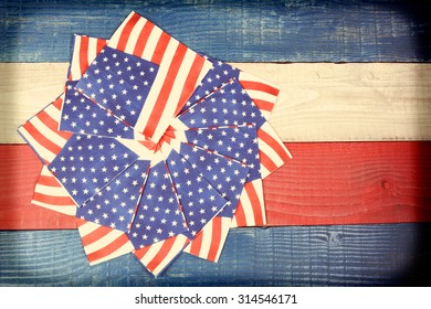 Instagram style shot of American Flag napkins spread out on a red, white and blue picnic table. Suitable for American Holidays: 4th of July and Memorial Day. Vignette effect added.