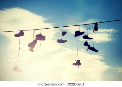Instagram style silhouettes of shoes hanging on cable at sunset.