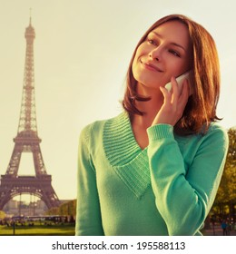 Instagram-like cross processed picture. France with Eiffel Tower in background. Cute beautiful Caucasian female model holding a phone in her hand and smiling.