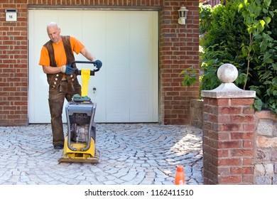 Installation of brick pavers on a driveway with a middle-aged man using a compacter to compact the paving in front of a garage door at the entrance to a property.
