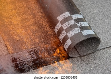 Installation by heating and melting of bitumen rolls by torch to flame while sealing the substrate against ascending moisture. Professional installation the waterproofing on the concrete foundation