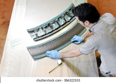 Installation of carbon fiber: worker manually realizes a component in real carbon fiber for automotive use. Creating a racing car pieces using a factory mold and meter for measurements. Above view.