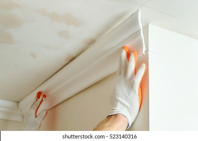 Installation of ceiling moldings. Worker fixes the plastic molding to the ceiling.
