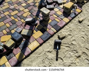 Installation of colorful bright paving slabs. Red, black and yellow sidewalk tiles 'Old Town' and rubber mallet for work