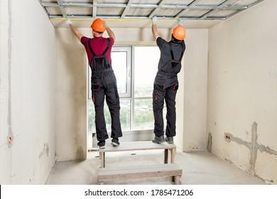 Installation von Trockenmauer. Die Arbeiter messen die Decke.