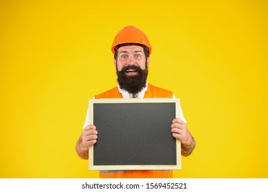 Installation of electrical equipment. Handsome repairman. Man bearded repairman builder work clothes. Responsibility and garanties. Engineer occupation. Repairman engineer hold blackboard copy space.