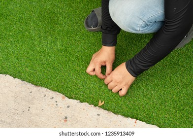 Installation of Green Artificial grass. Worker install soft artificial turf on backyard