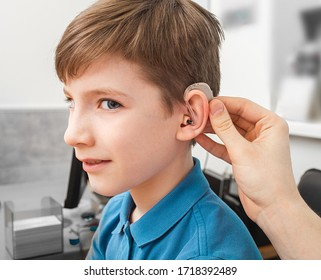 Installation hearing aid on сaucasian boy's ear. Hearing treatment at clinic