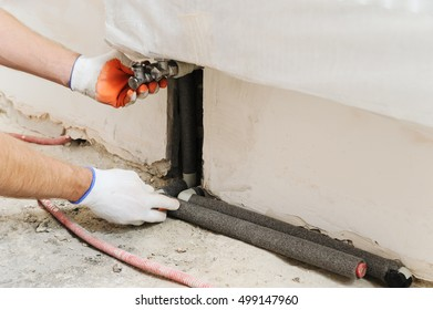 Installation of home heating. A worker attaches the pipe to the radiator.
