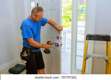 Installation of a lock on the entrance door Hand 's man with screwdriver Installs door knob.