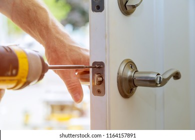 Installation locked interior door knobs, close-up woodworker hands install lock.