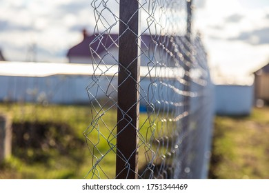 Installation of a metal mesh on the fence in the country.