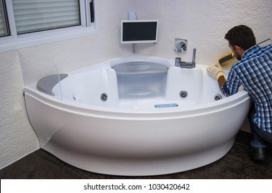 Installation of modern bath, (hot tub), applying sealant, bathtub with tv.
