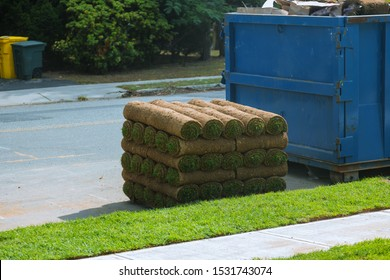 Installation of a modern landscape stacks of sod rolls for new lawn and dumpster full garbage container residential building construction home
