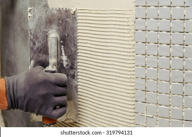 Installation of mosaic tiles. The worker puts adhesive on the base